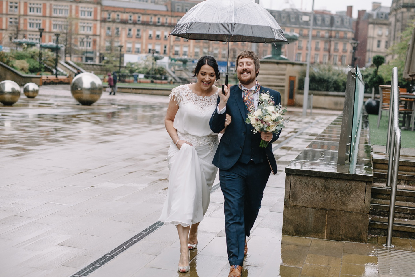 Bride and groom walking in the rain through Sheffield Peace Gardens
