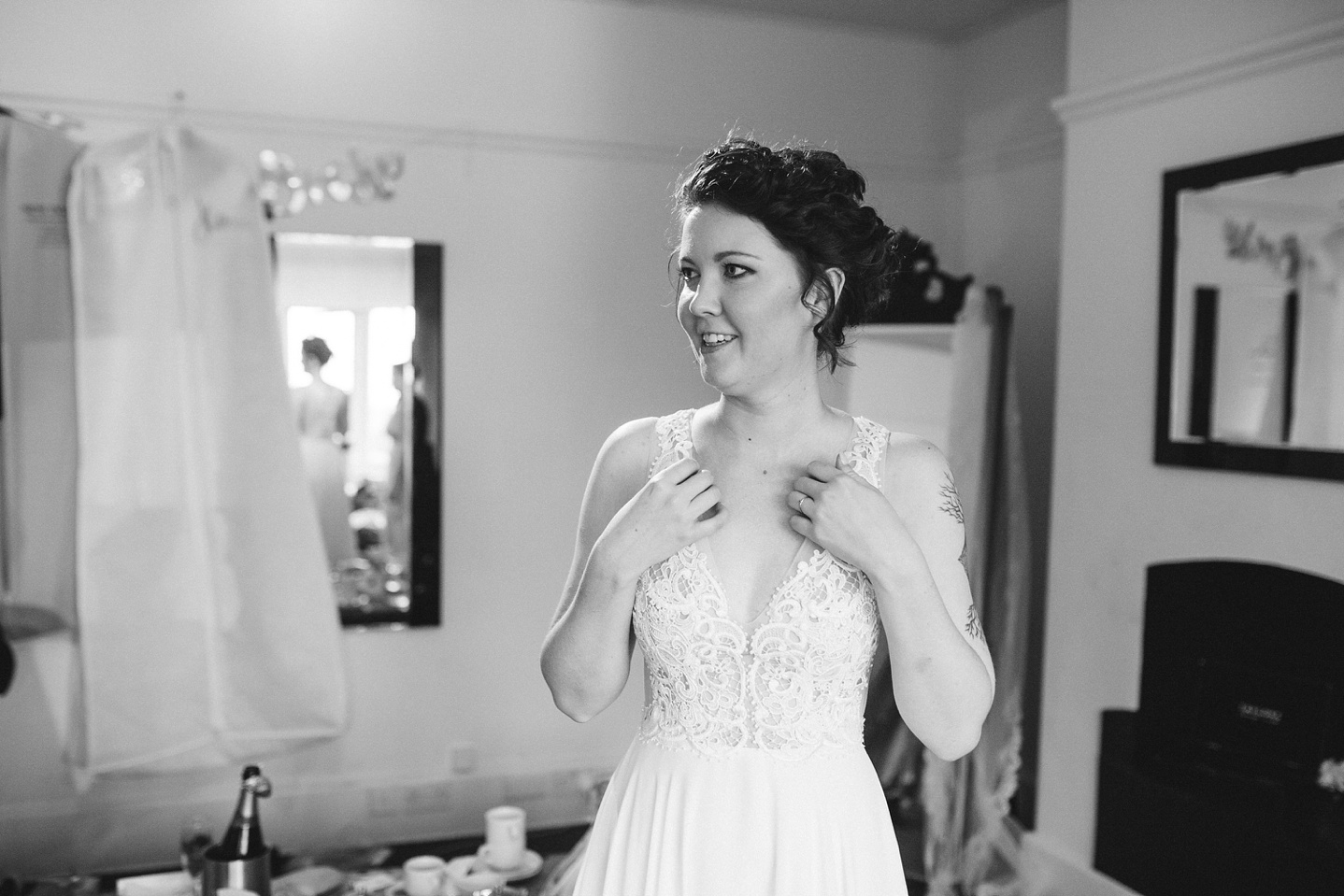 black and white image of bride smiling whilst getting ready into her wedding dress at Whirlowbrook Hall