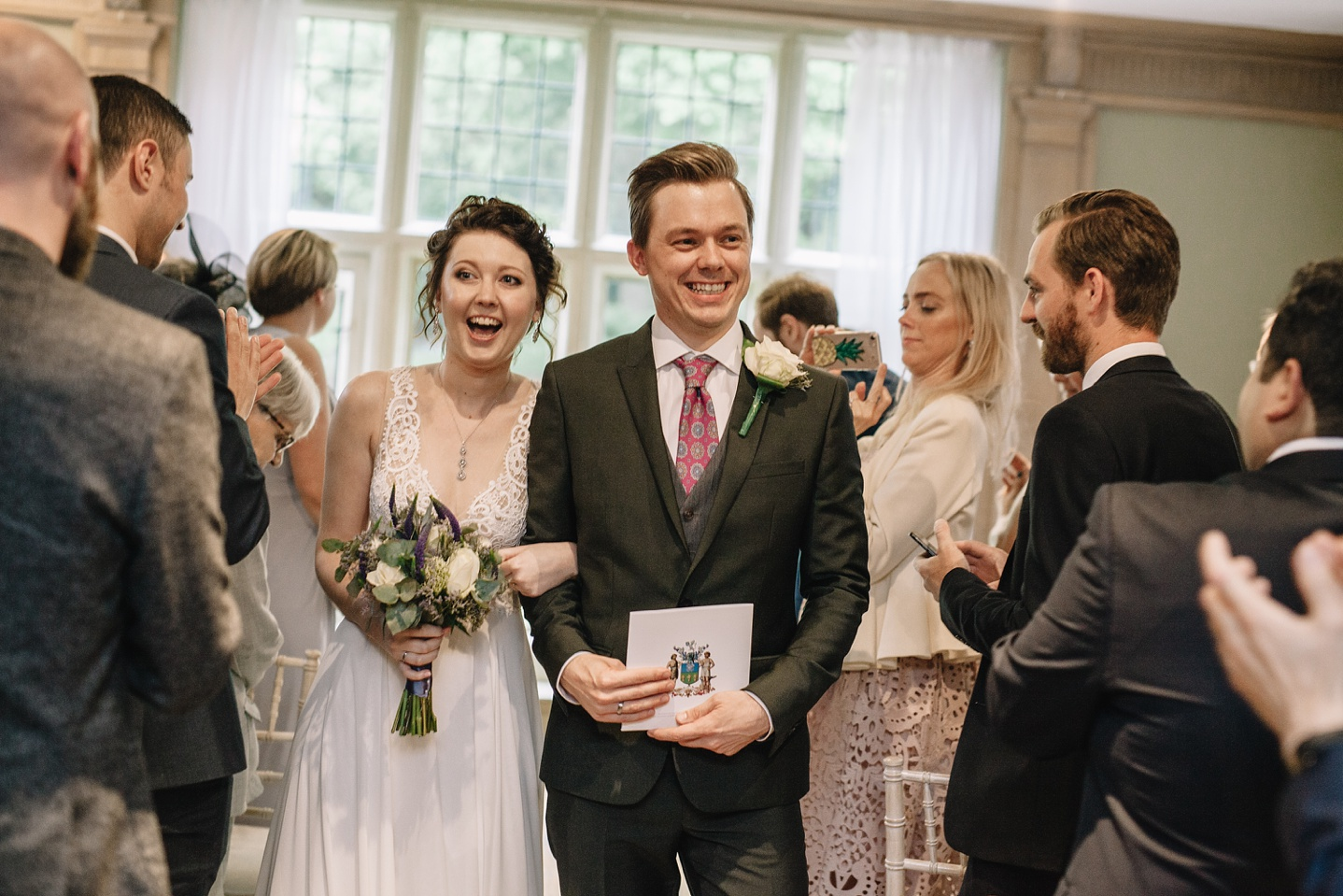 bride and groom laughing whilst walking down the aisle