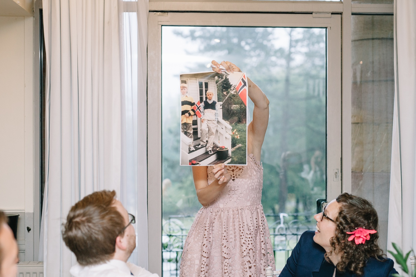 grooms sister holding up embarrassing childhood photo of groom