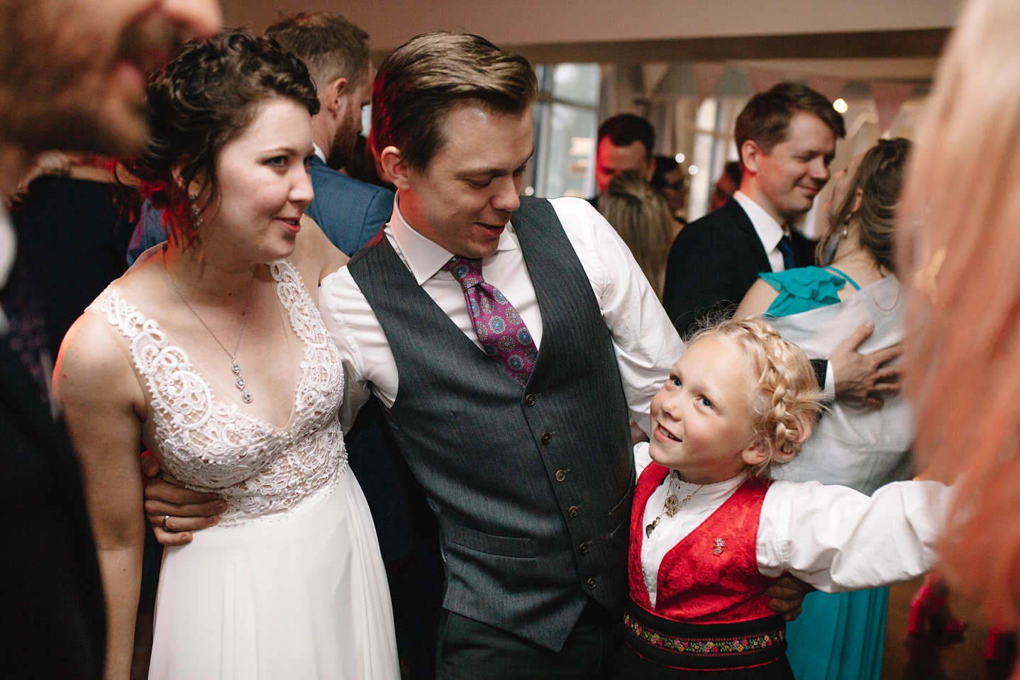 bride and groom dancing with little girl
