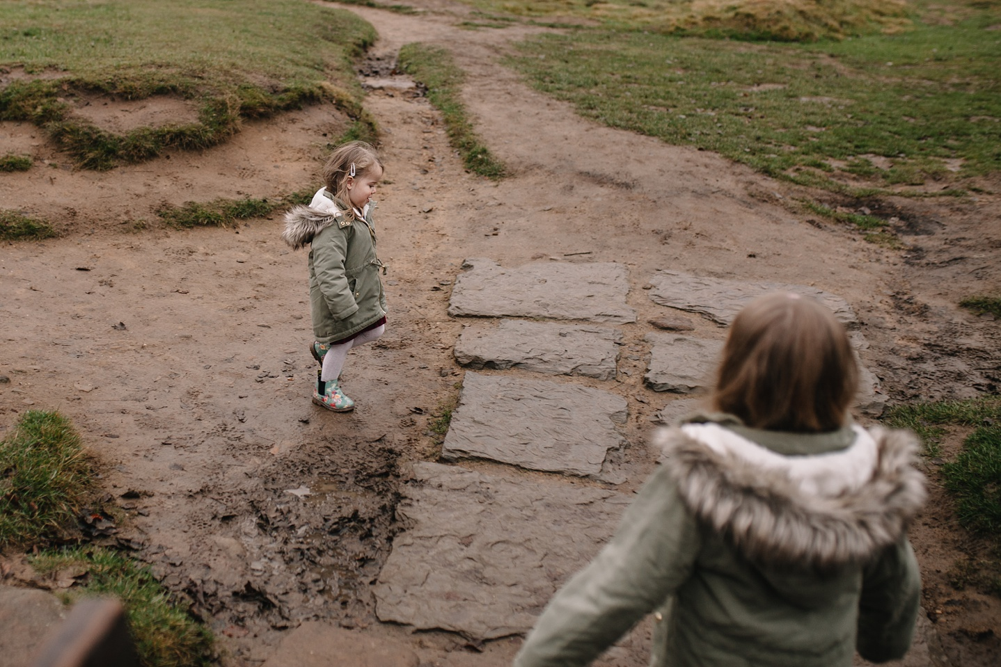 natural family photography or two little girls playing in the mud