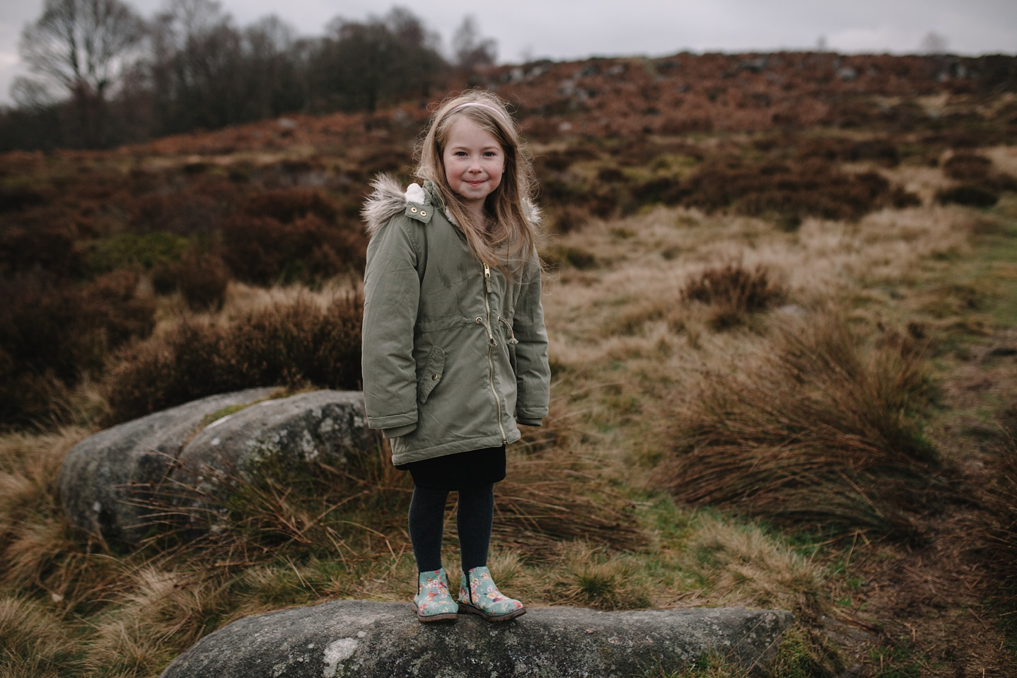 little girl stood on a rock smiling at the camera