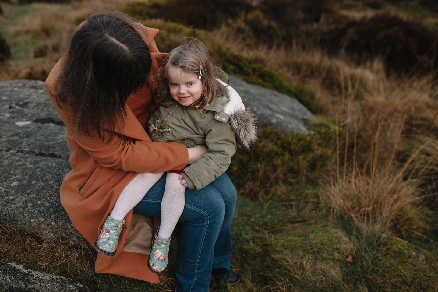 family photography of little girl sat on mums knee smiling at the camera in Sheffield