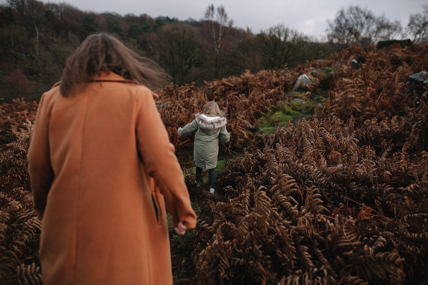 mum and little girl walking through the brown ferns