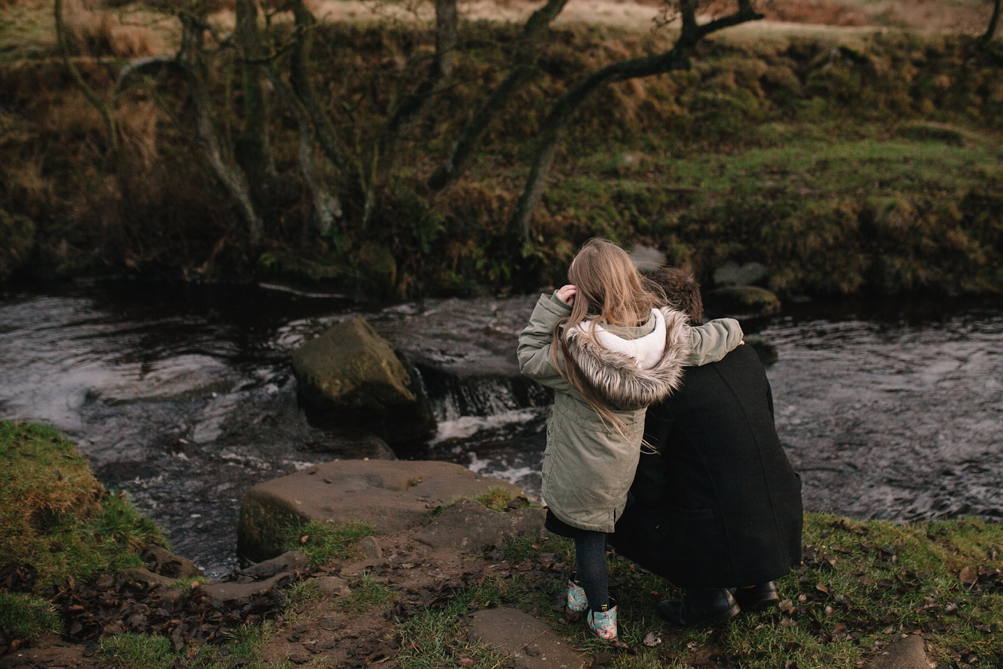 dad crouched down with little girl looking at the river
