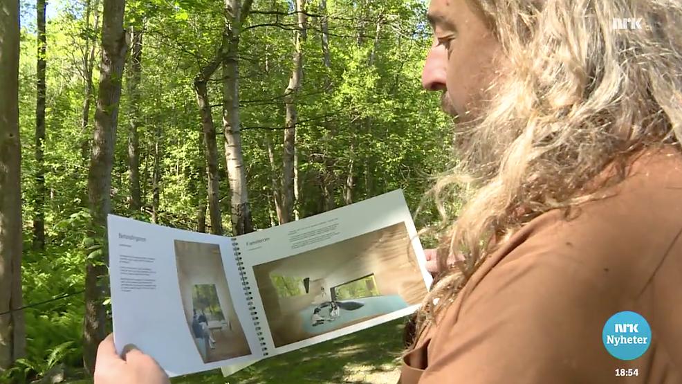 Håvard viser planene for hytta i naturomgivelsene.
