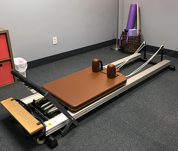 The Pilates Reformer uses springs, straps and pulleys to challenge and support the body.