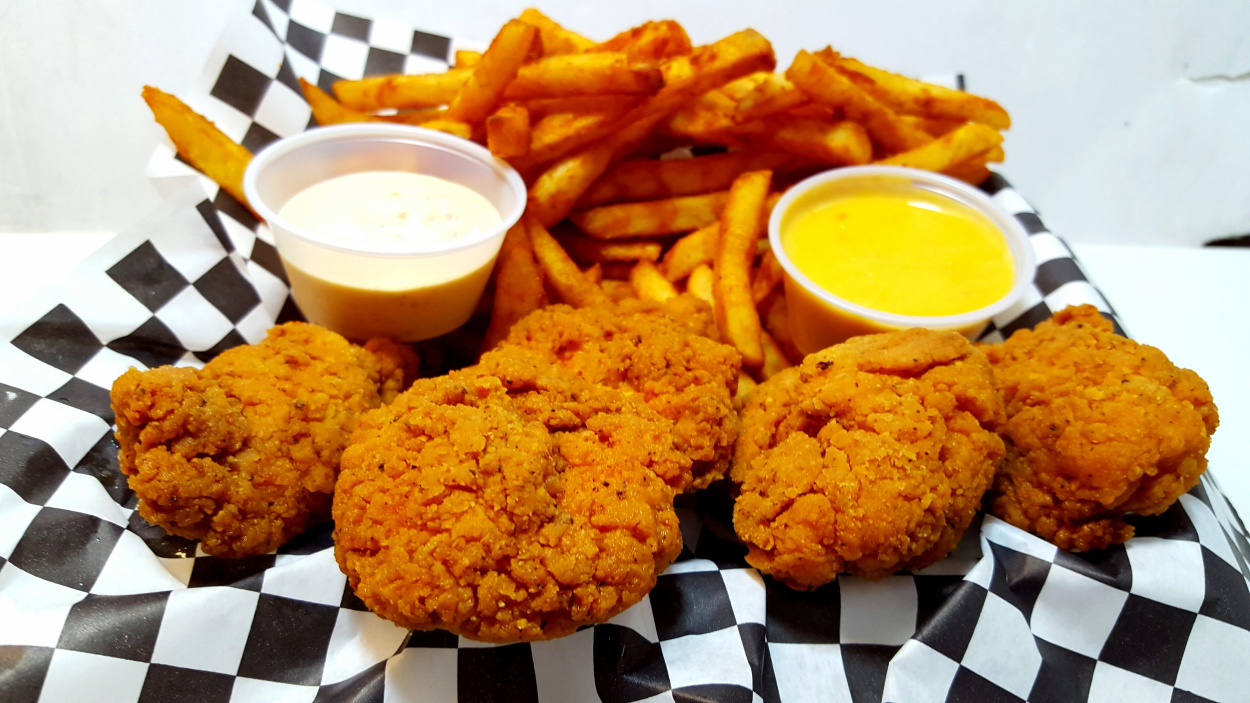 CHICKEN TENDER BASKET:  Four crispy chicken tenders fried to perfection with a side of seasoned battered fries, and your choice of homemade melted  queso and jalapeño ranch .