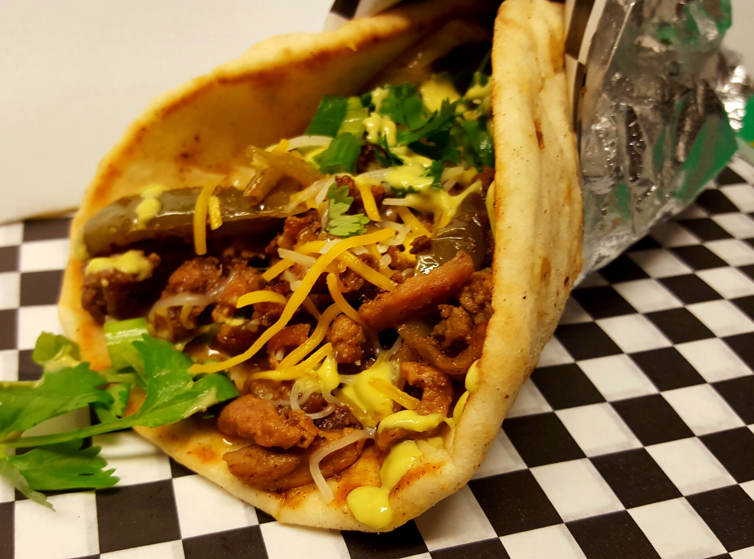 MEXICAN PITA: A soft pitta bread stuffed with   MEXICAN FRIES A bead of seasoned battered fries with melted homemade queso topped with Mexican beef and pork fajitas steak, grilled bell peppers and onions, cheddar and monterey cheese, green onions, cilantro and o    ur mouth watering Mexican hot green salsa.