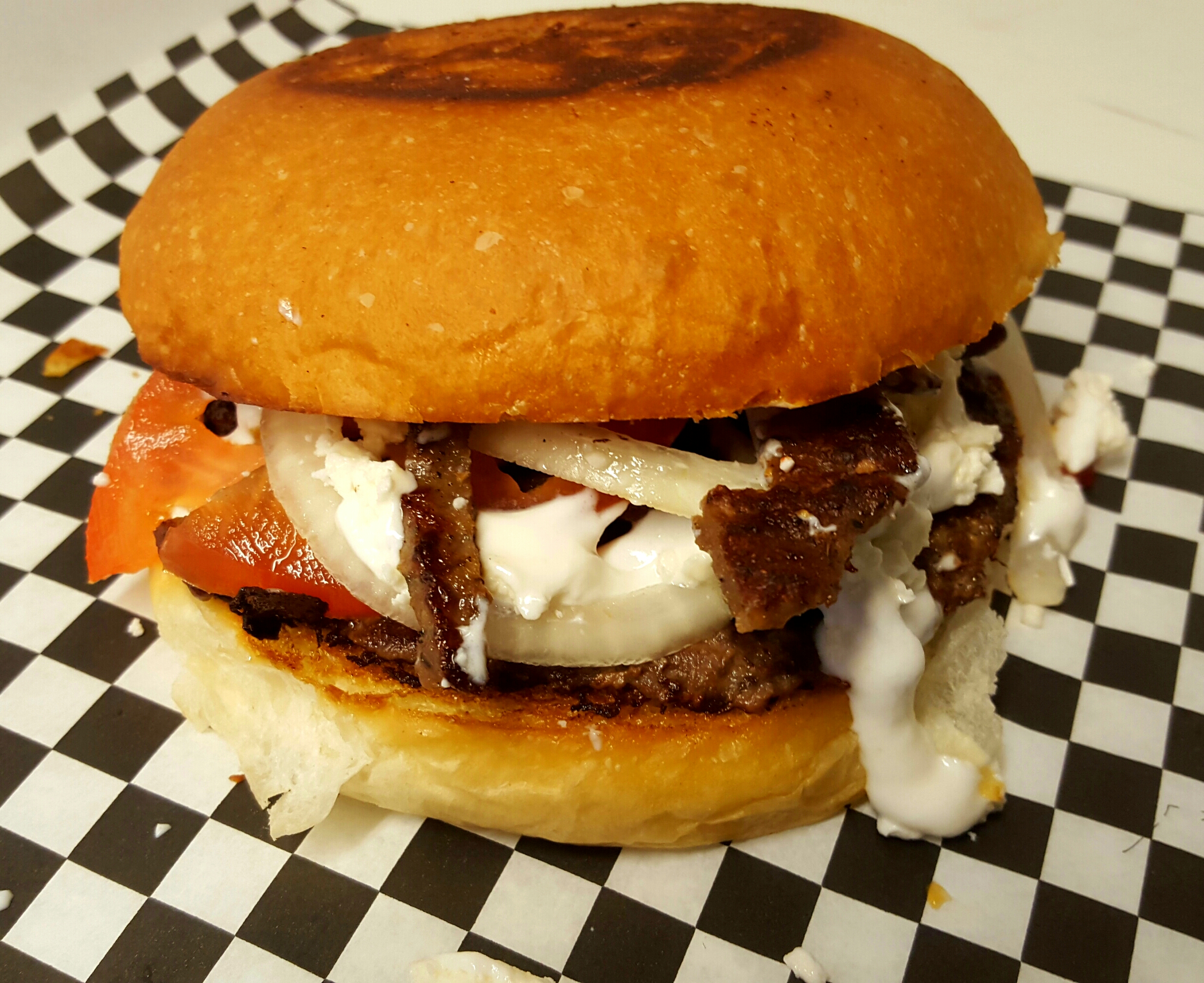 GREEK BURGER: A 1/3 lbs homemade beef pound patty, topped with Greek gyro meat (lamb and beef), fresh onions, tomatoes,     tzatziki    sauce, topped with    feta cheese.