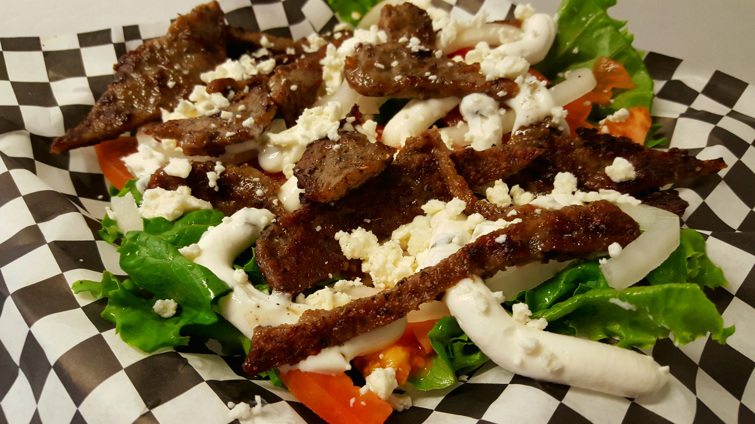 GREEK SALAD: A bed of crisp lettuce, tomatoes, onions topped with gyro meat ( lamb and beef ) and feta cheese.