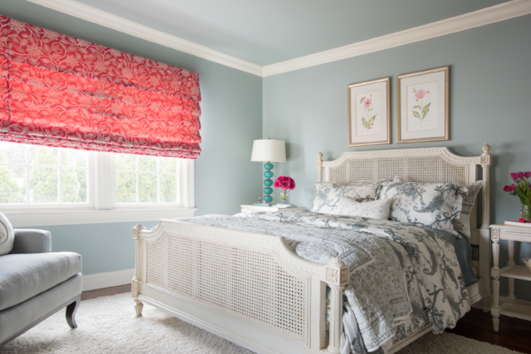To create cohesion between the window treatments and the rest of the room, we framed two pink drawings with warm, gold frames and added flowers to both nightstands.