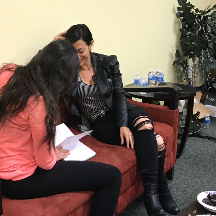 Workshop participant sitting with Alana to review her writing and develop her song.