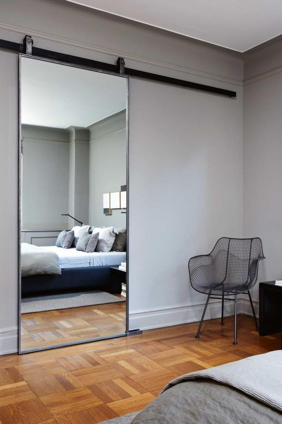 A large mirror and a door into the walking cupboard