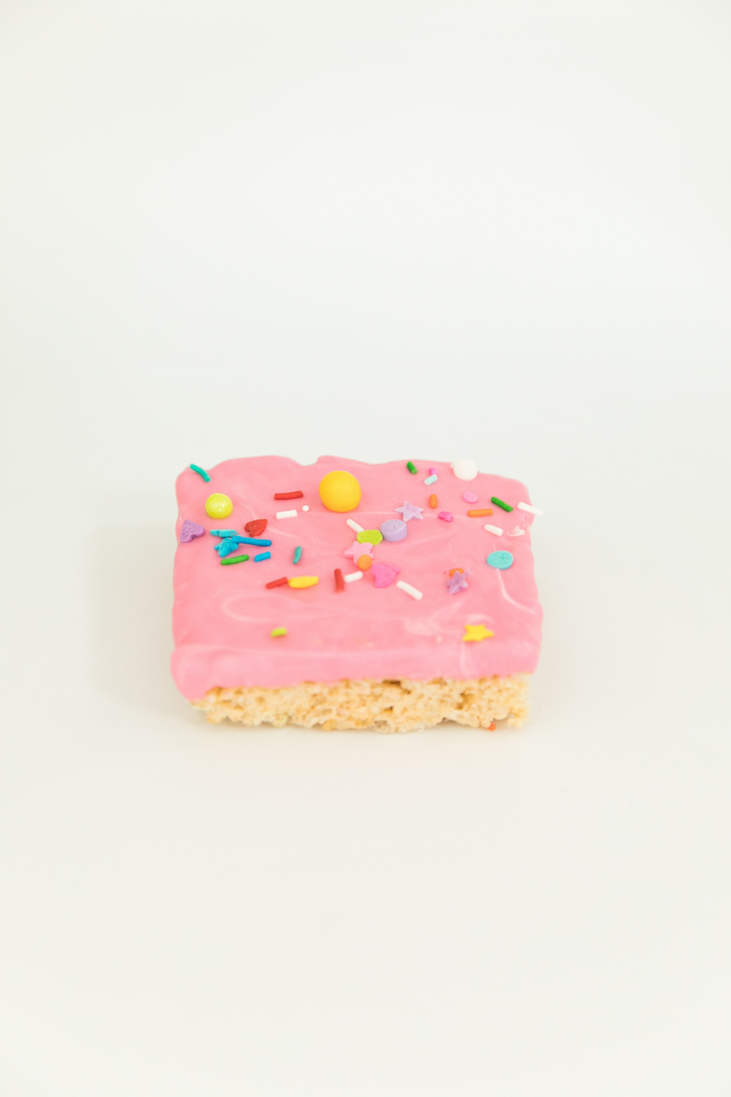 rice krispies treat dipped in pink white chocolate with sweetapolita sprinkles