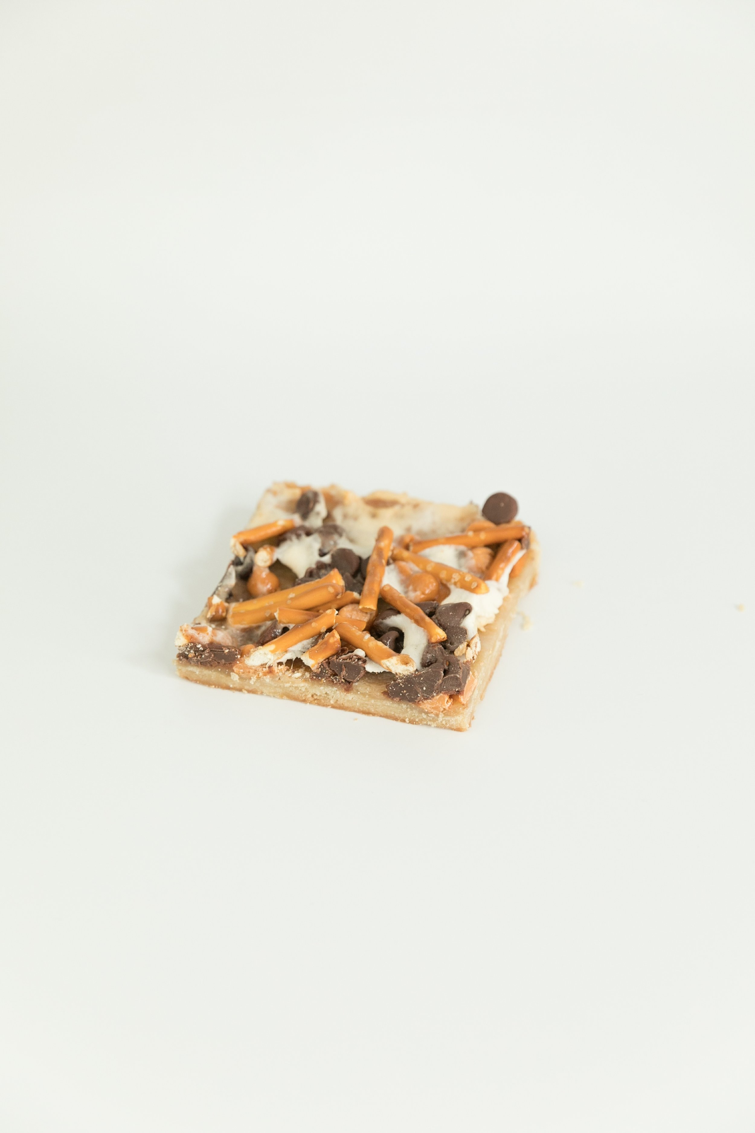 pizza bars topped with pretzels, white chocolate chips, chocolate chips, marshmallows and a cookie bottom.