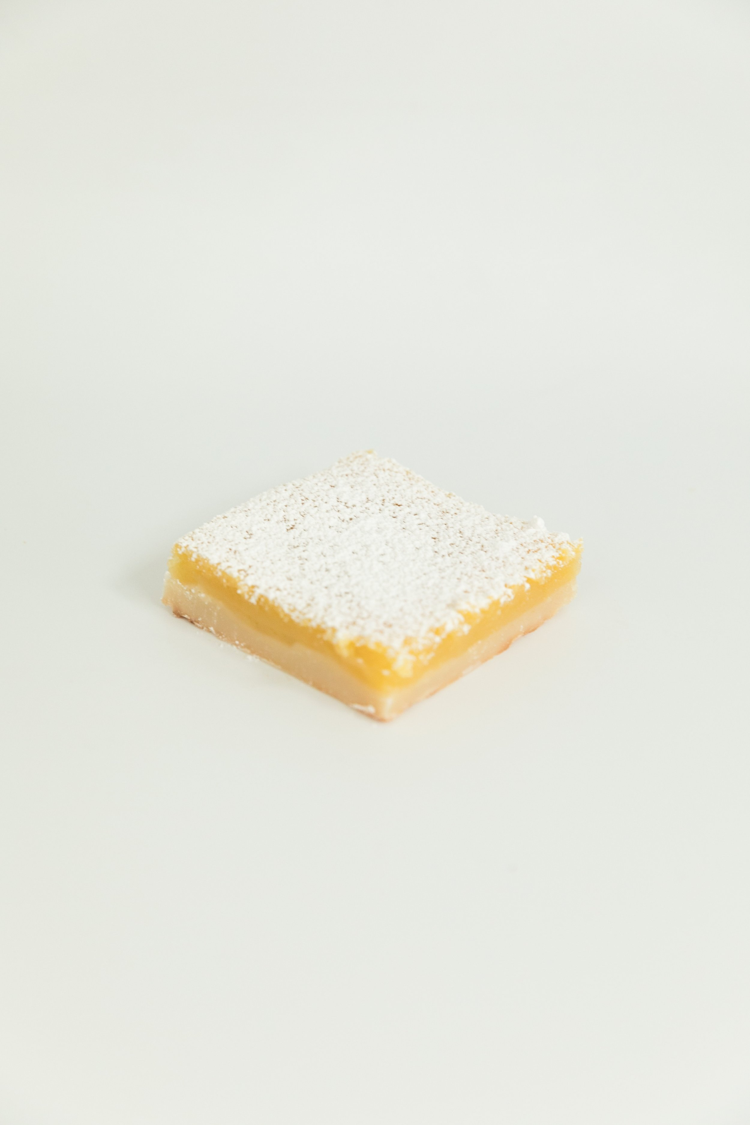 lemon bar topped with a powdered sugar sprinkle