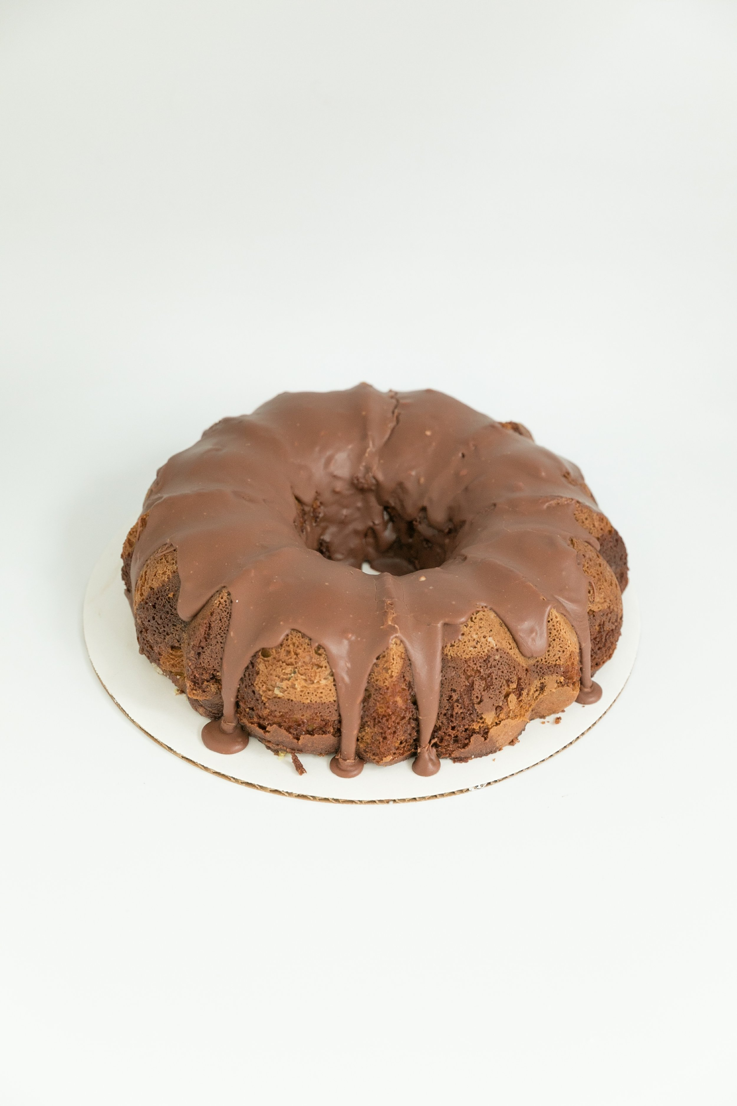 Old-fashioned pistachio bundt cake topped with a chocolate ganache.