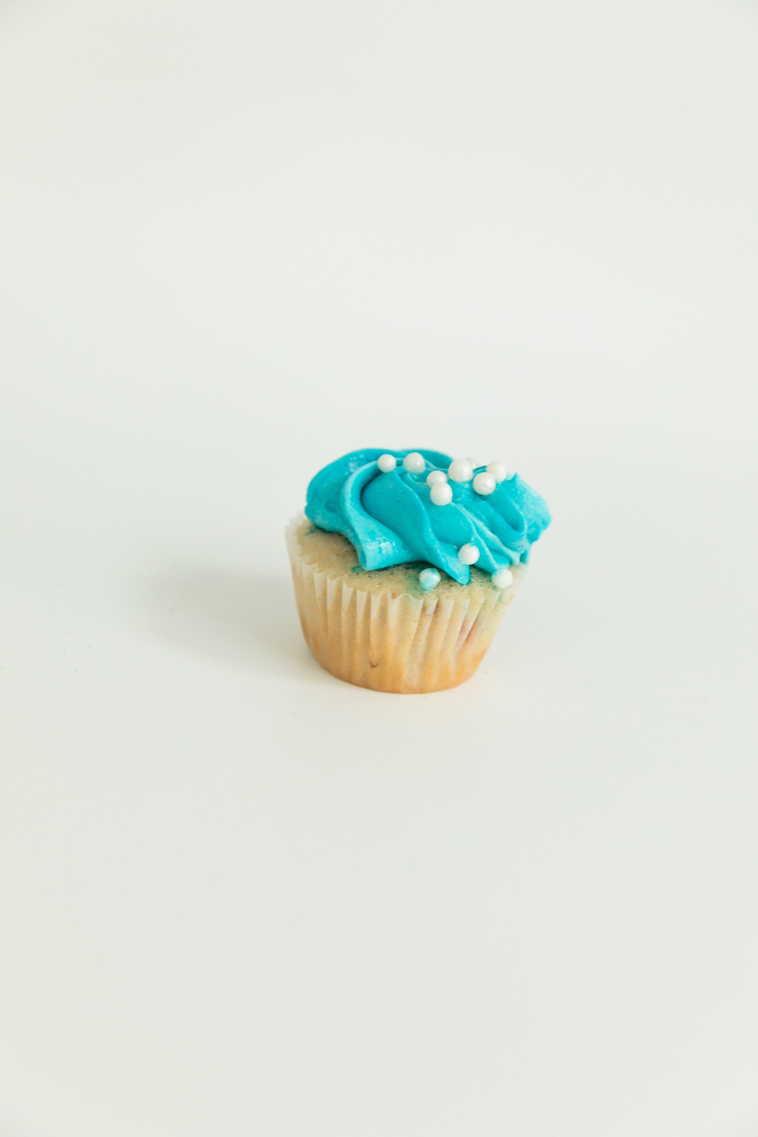 vanilla cupcake with blue vanilla buttercream and pearl sprinkles