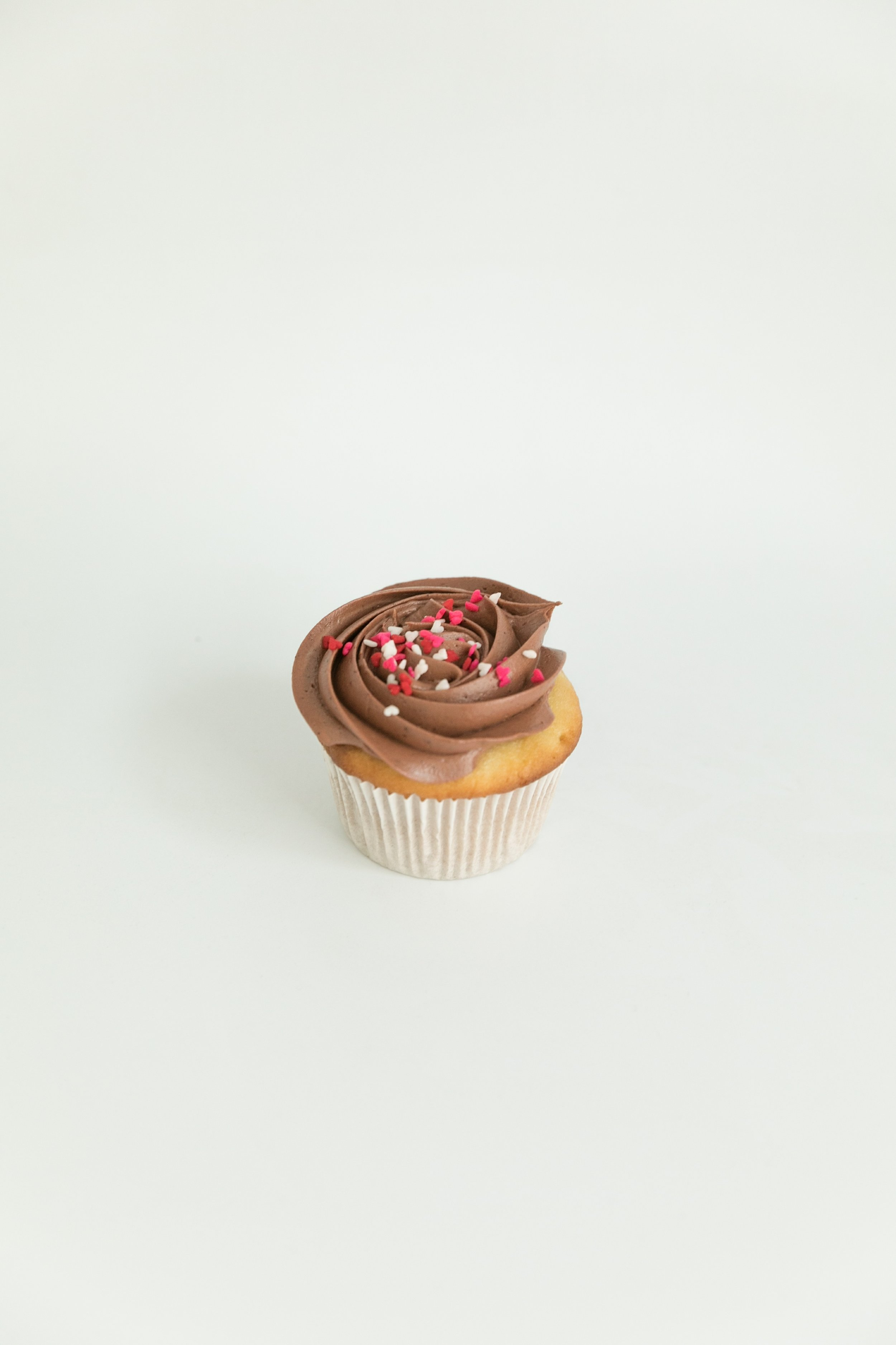 Vanilla cupcake with chocolate buttercream and heart sprinkles