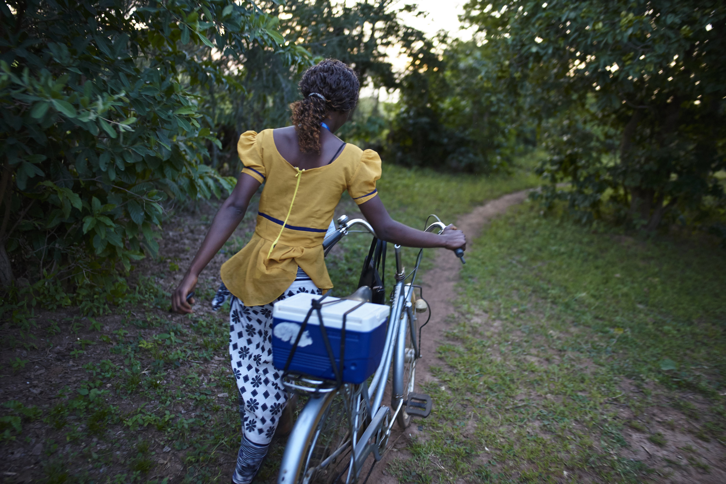 Community Health worker carrying a sputum collection container during screening and linkage activities within the community
