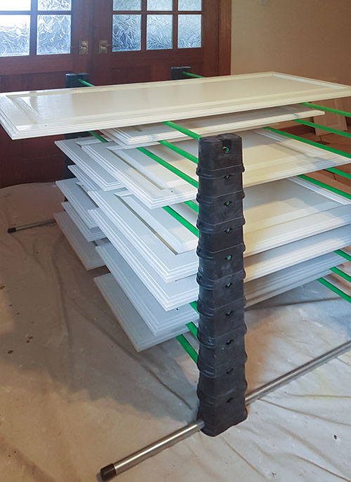 Stacking doors to dry while painting a kitchen by hand.