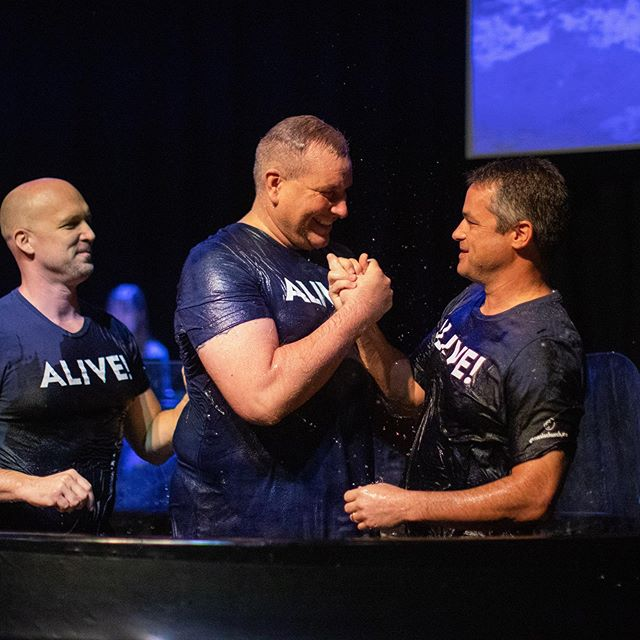 """➡️➡️ swipe through to see everyone who was baptized! We got to enjoy fathers baptizing sons, mothers baptizing foster daughters, big brothers baptizing little brothers, and so much more. What a day in the Kingdom. Dead to sin, alive in Christ.  What Genesis believes about baptism: baptism is for anyone who has decided to trust Christ alone for salvation. The word baptize means to """"dip or immerse"""" under water. Jesus modeled this form of baptism and commanded it, making baptism a symbolic act of obedience and faith. Anyone who has professed faith in Christ should be baptized at his or her conversion or soon after. (Read further—Matthew 3:16, Matthew 10:32, Matthew 28:19, Acts 2:38, Acts 8:35-38, Romans 6:3-4, 2 Corinthians 5:17)"""