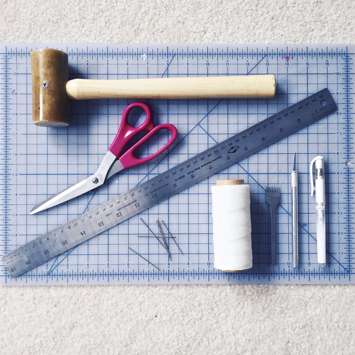 Waxed-nylon thread, chisel, rawhide mallet, X-Acto knife, white pen, leather needles, self-healing mat, fabric scissors, ruler