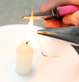 - An angle that is slightly larger than 90 degrees works well.Remember that the needle will be hot, so place it on a heat-resistant surface to cool down once you've bent it to the angle you'd like.