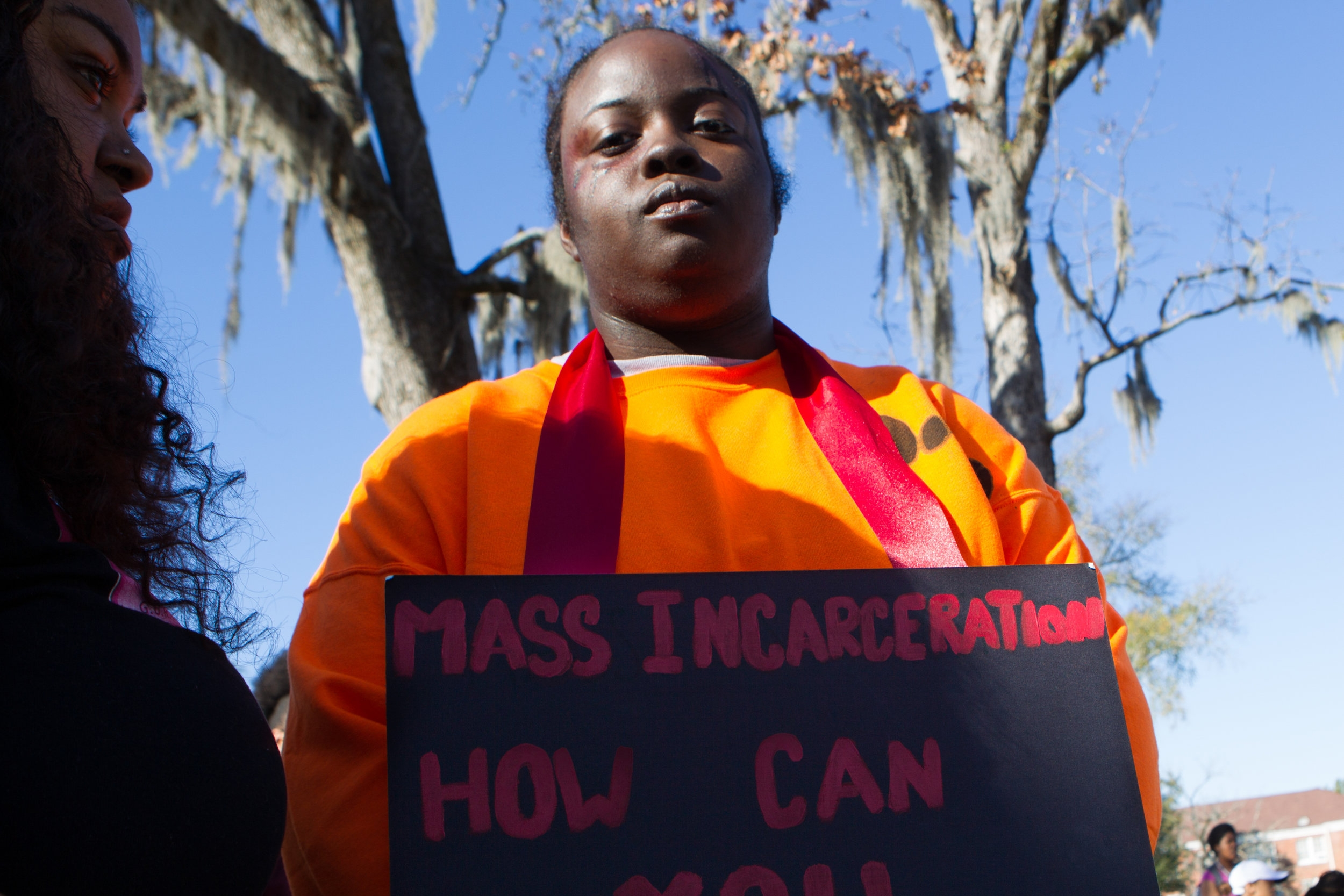 Student wearing prison uniform in protest of mass incarceration.