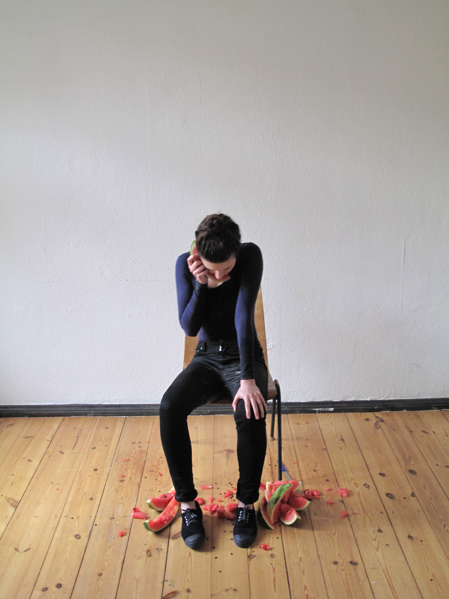 Hear This, 2012  Single-channel digital video, colour, sound  8mins 5 seconds.  Lauren Brincat's video  Hear This  depicts the artist alone in her studio during a residency in Berlin, speaking on a telephone to her mother back in Australia. The telephone is made from watermelon wedges that the artist slices and consumes as she speaks, literally eating her own words in a forlorn yet comical representation of homesickness. As the video progresses the watermelon soaks Brincat's clothes and dirties her hair and face, creating a disquieting and awkward performance.  Sound plays a significant role in  Hear This , as in many of the artist's works. The soundtrack acts as an emotive device, drawing on both personal and cultural recollections. Unassuming noises such as the cutting of a slice of melon, or a seed falling onto the wooden floor, take on greater importance in the video, emphasising both the solitude of the figure and the intimacy of the performance.