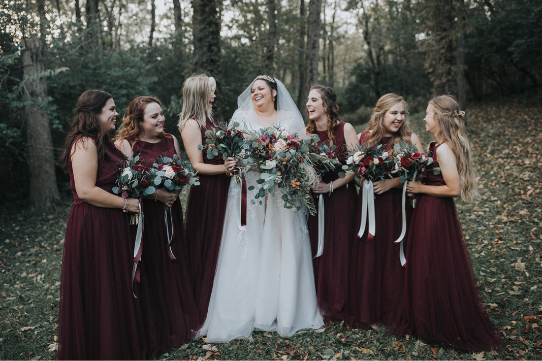 A bride and her bridesmaids in burgundy dresses and laughing