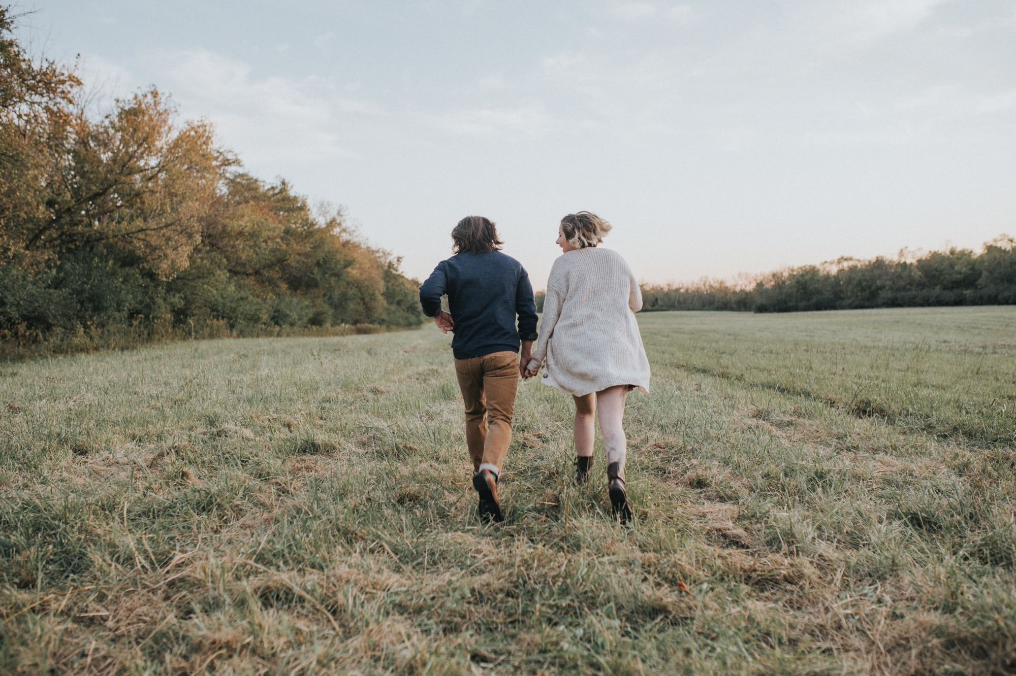 couple having fun and running through a field in Ohio