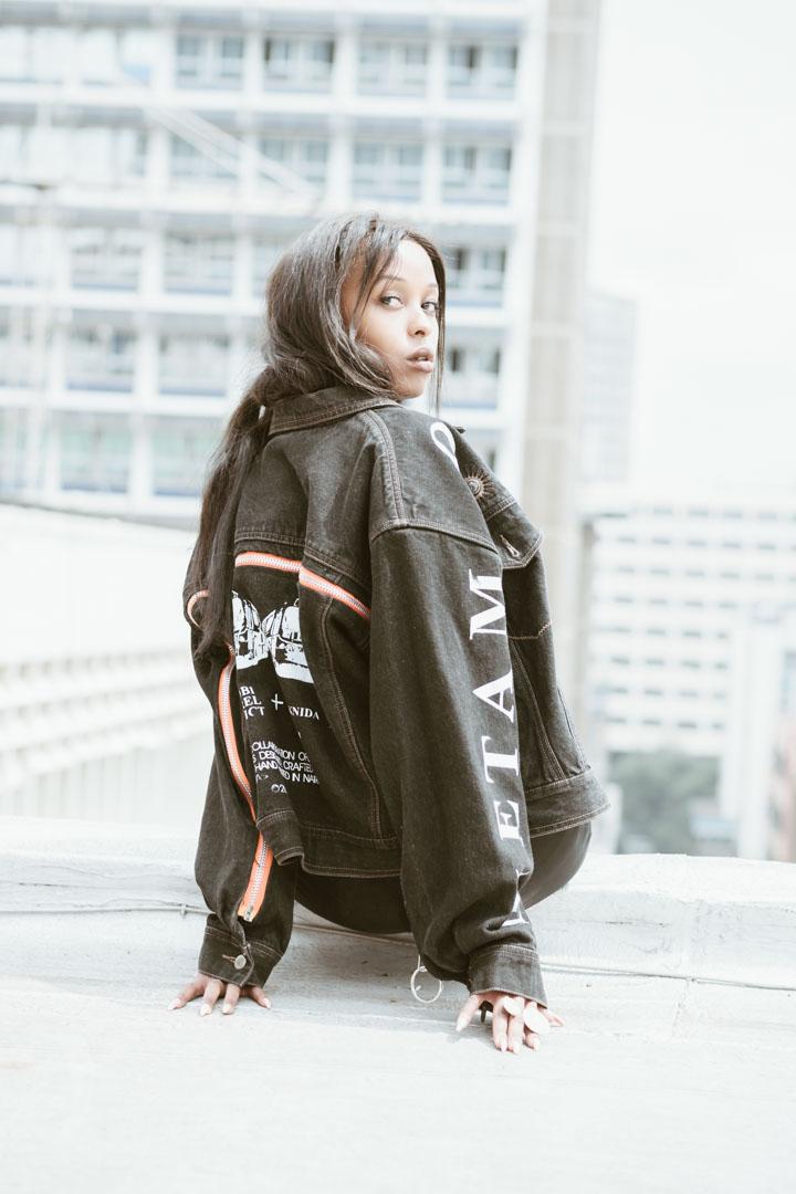 Anne Mwaraua in Non-TelevisedTM Limited Edition Charcoal Black Unzipped Denim Jacket