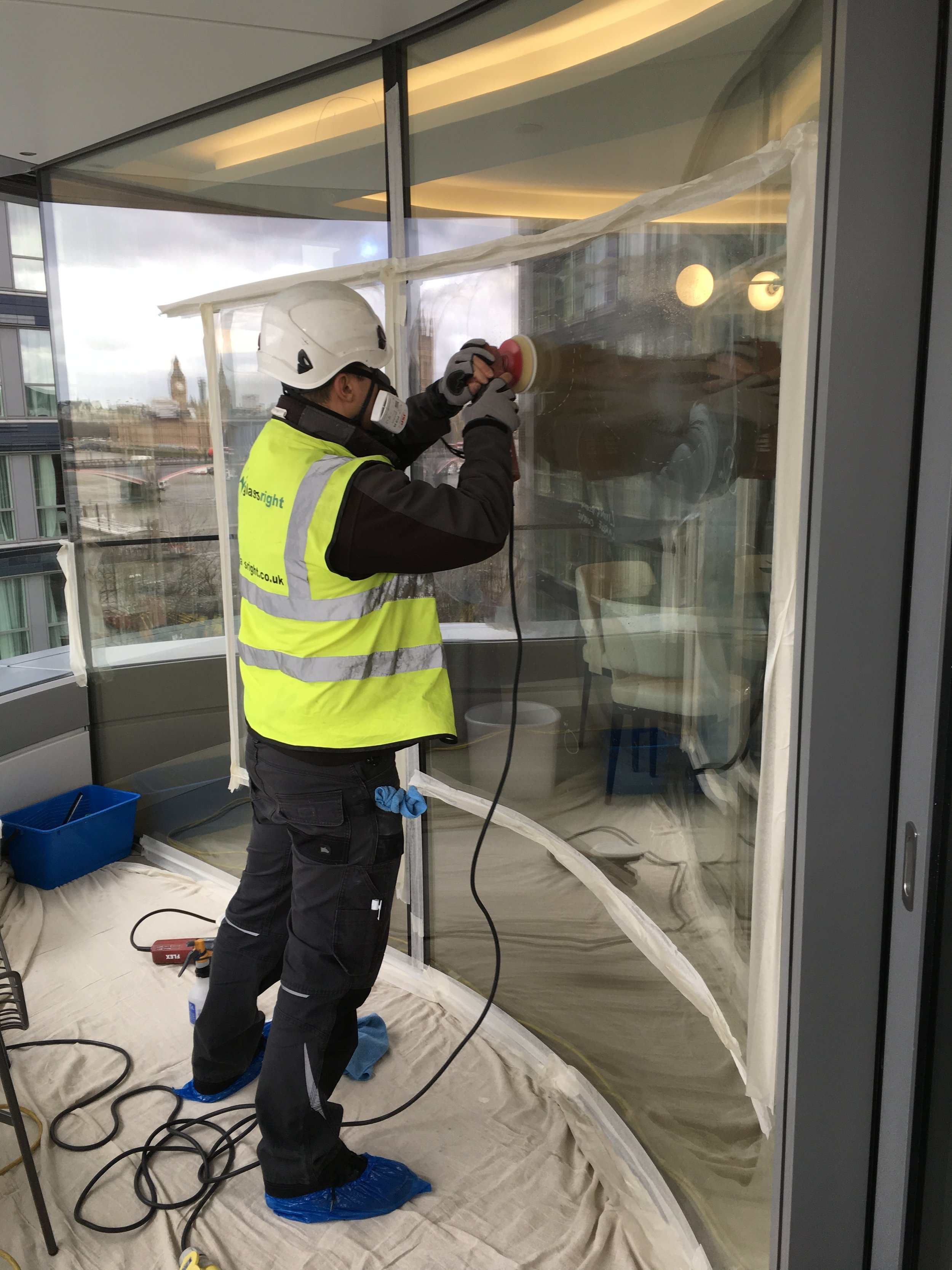 Polishing to external face of curved glass structurally bonded to balcony.