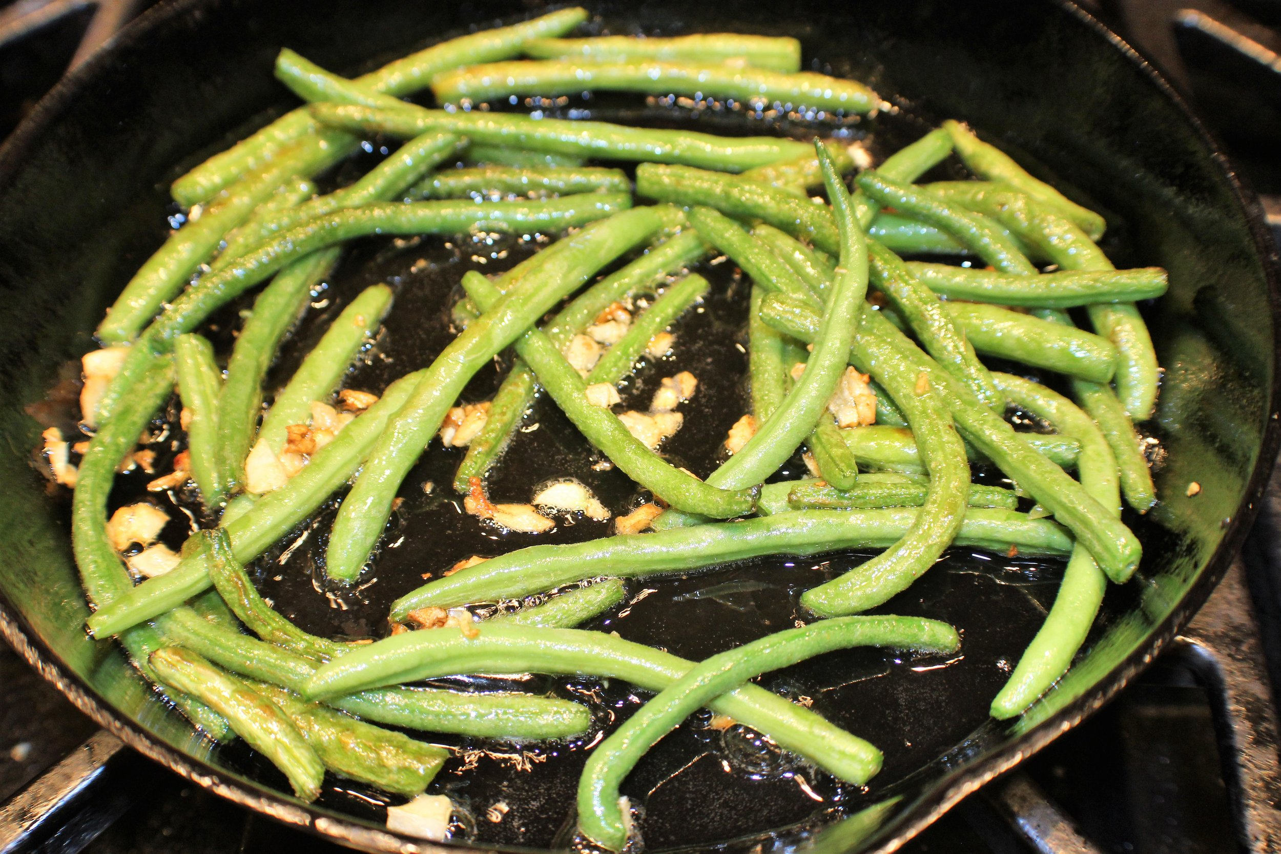 1 lb. green beans, trimmed  1 clove garlic  olive oil  salt  Add the beans to boiling, salted water and allow to cook for four or five minutes. Drain and cool by running under cold water in a colander.  Smash the garlic clove and mince roughly. Heat a cast iron skillet and film it with olive oil. Add the green beans and cook on medium-high heat for about 5 minutes. Add garlic and continue to cook, turning and stirring until the beans begin to char. Turn off the heat and salt the beans to taste. Enjoy warm or at room temperature.  ©Kate Jerome 2019
