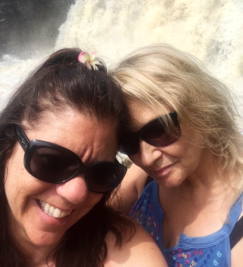 Coleen Elwood and Tara Cindy Sherman smile in front of a waterfall.