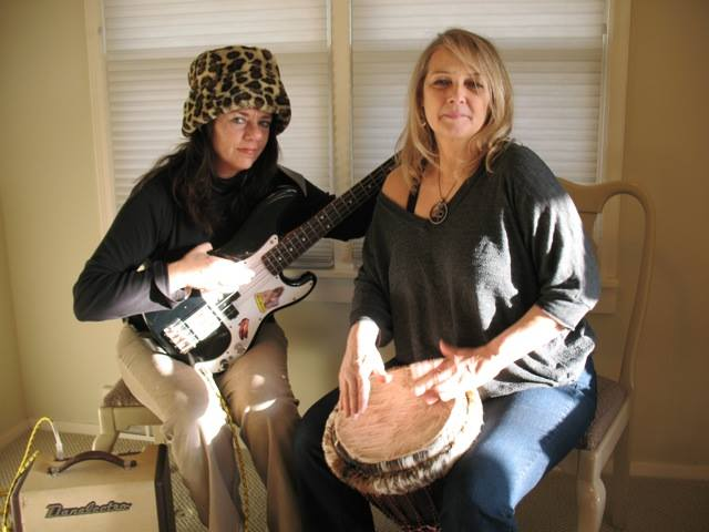 Coco Elwood plays bass and Tara Cindy Sherman play the djembe drum in a Minneapolis jam session.
