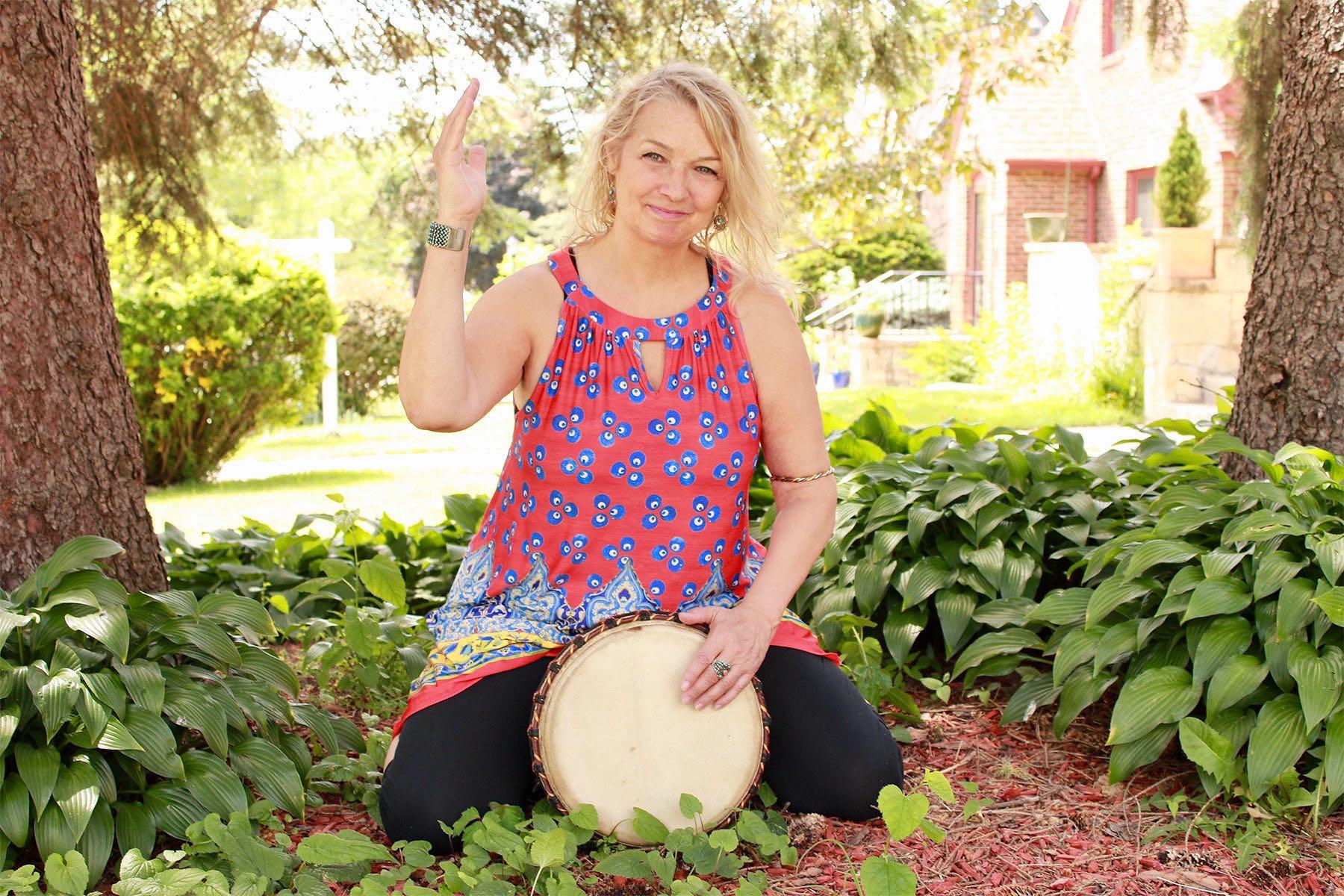 Tara Cindy Sherman playing a Djembe drum in her garden.