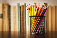 wire-desk-tidy-full-coloured-pencils-standing-wooden-table-front-bookshelf-books-shallow-dof-32411822.jpg