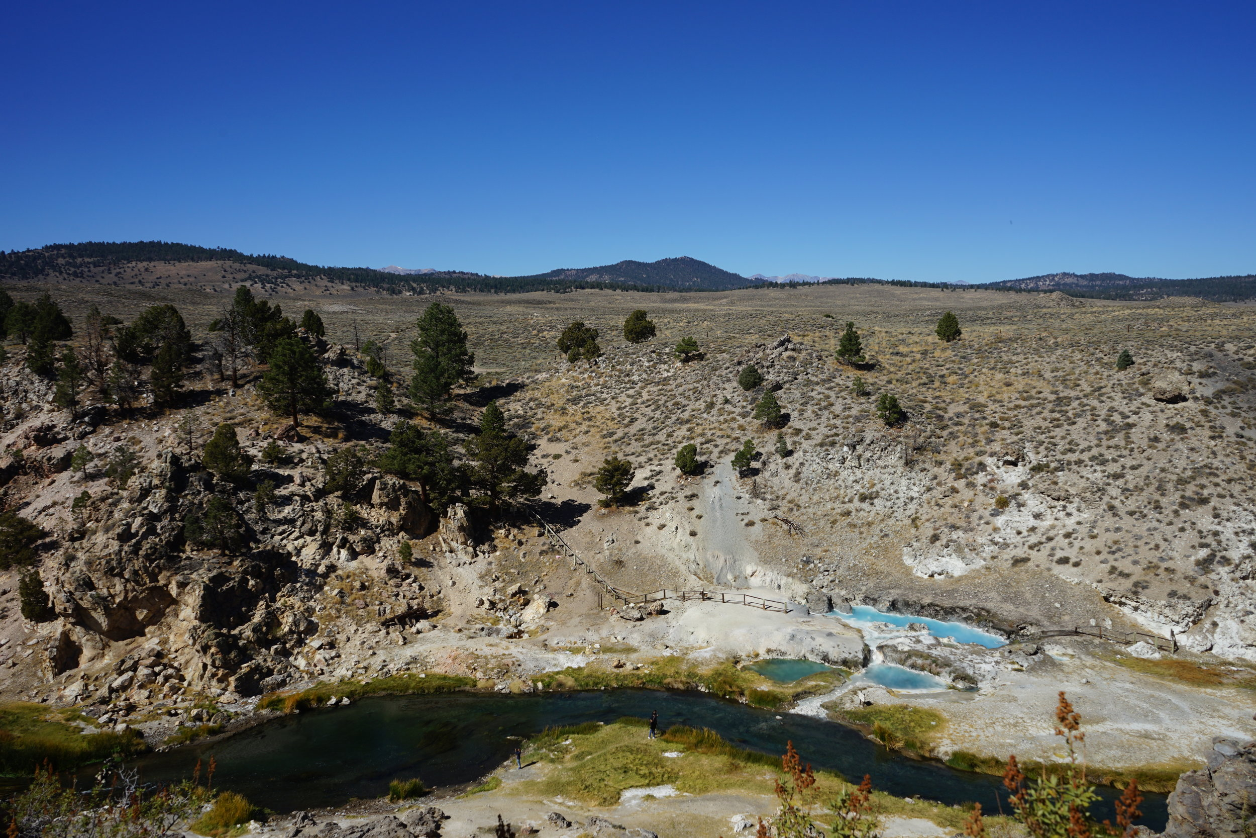 Hot Creek thermal springs in the Long Valley Caldera. The gap in solid bedrock outcrop on the far stream bank corresponds to a fault zone, in which damaged rocks are more susceptible to weathering. The spring, which appear to emanate from this fault zone, has fluctuated in temperature and flow rate over the years due to volcanic unrest. Don't go swimming in this one unless you want to end up like that couple in Dante's Peak!