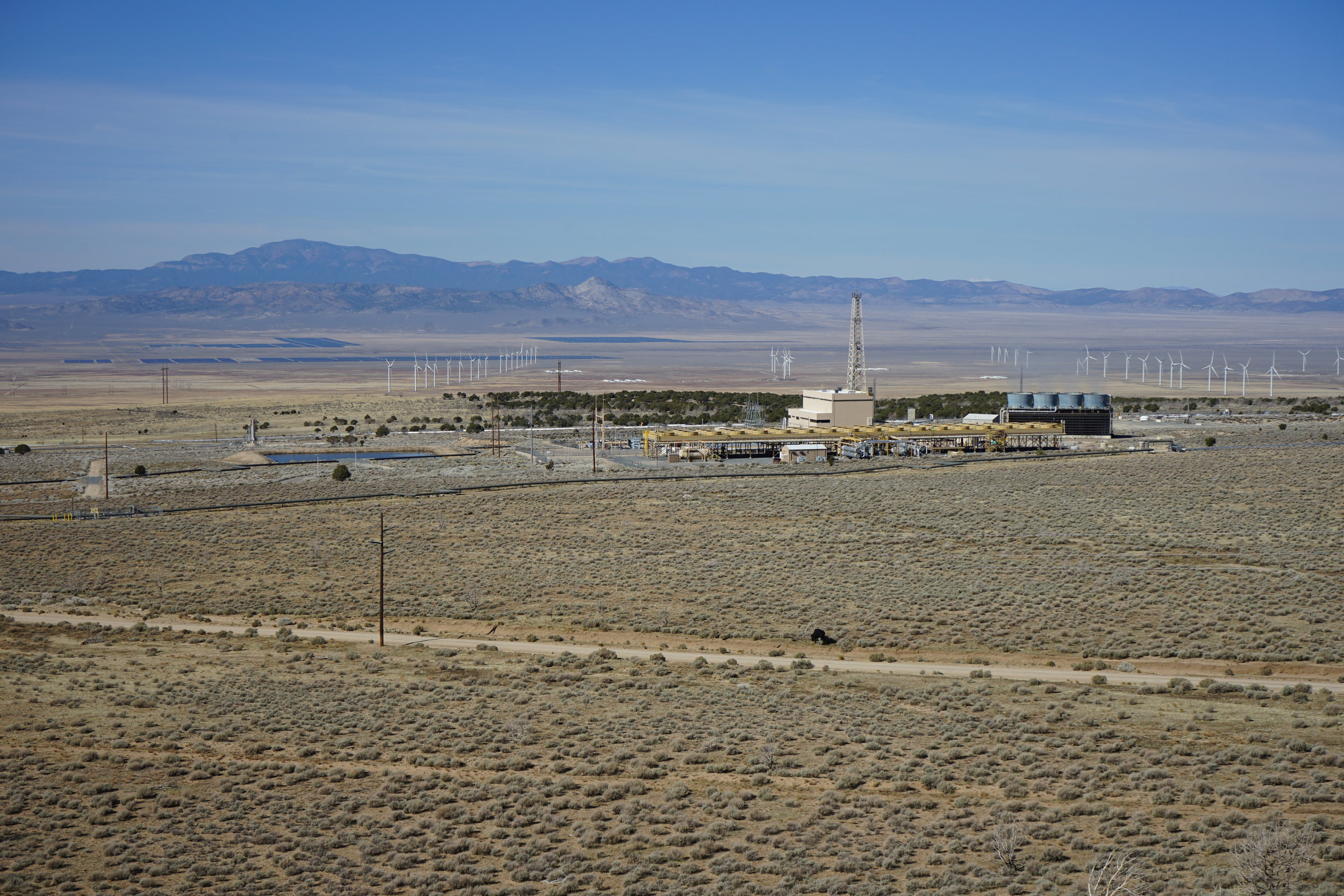 The Milford Renewable Energy Corridor, looking WNW. In the foreground, the Blundell Geothermal Power Plant produces 34 MW of power from a hydrothermal system that appears to be bounded by a steep fault that roughly corresponds to the treed hillside behind the plant. The Milford FORGE site will be between the rows of wind turbines on the right side of the image. Across the valley, a large solar farm also produces electricity.