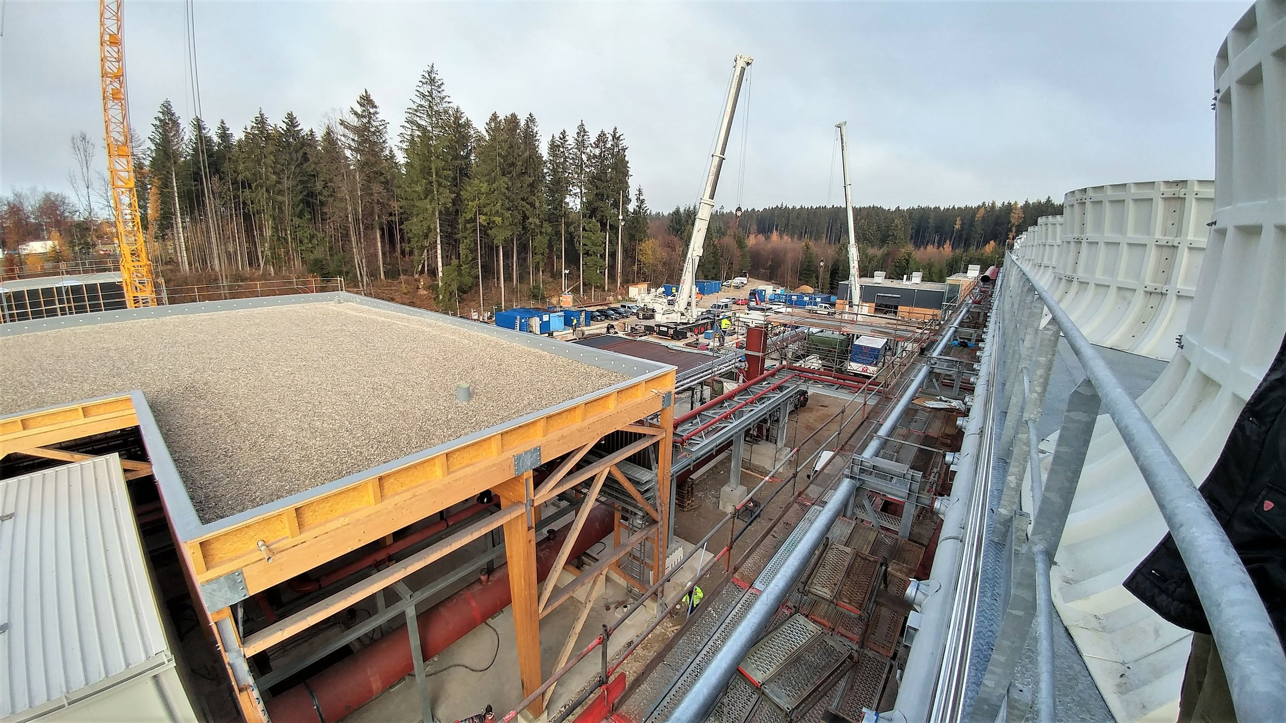 Holzkirchen site overview from the cooling towers. From left to right: power plant, geothermal well pad, district heating distribution center