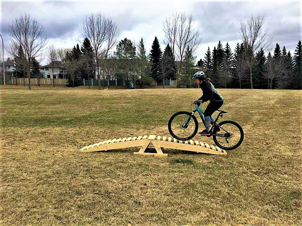 Katie pedals over a rounded a-frame. Eyes up, body strong and balanced!  Photo cred: Cranky's Women's MTB Club