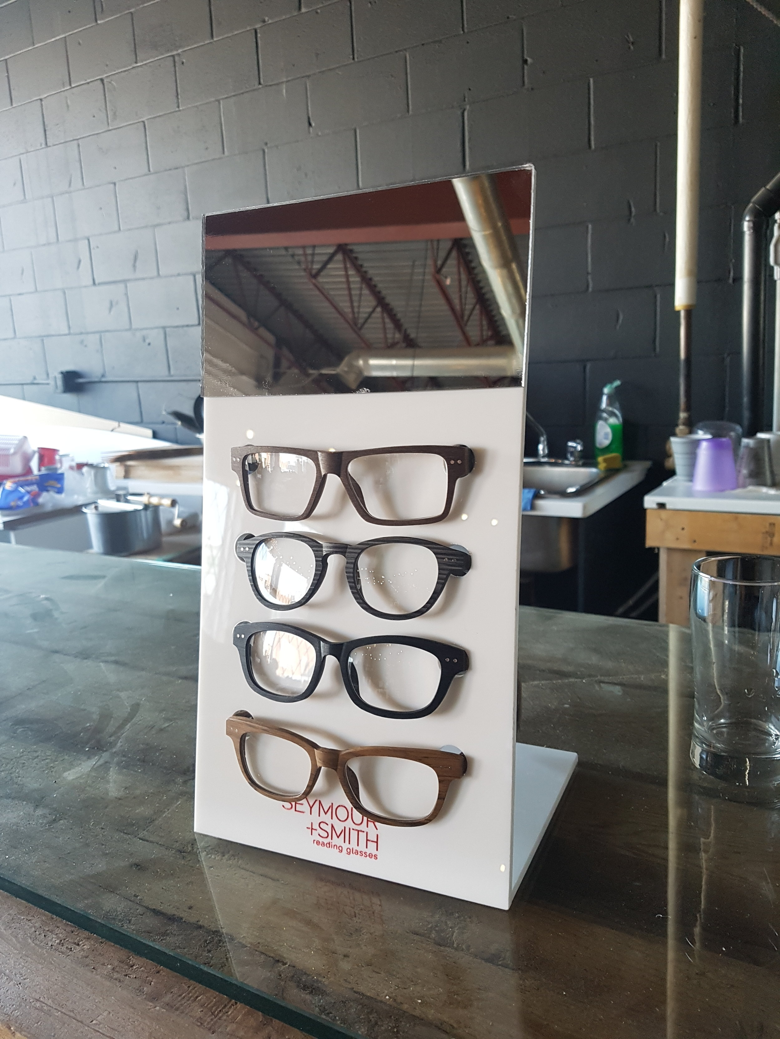 Eyewear Display. White Acrylic with Mirror and Paint Filled Branding.  Seymore&Smith Eyewear, Vancouver B.C
