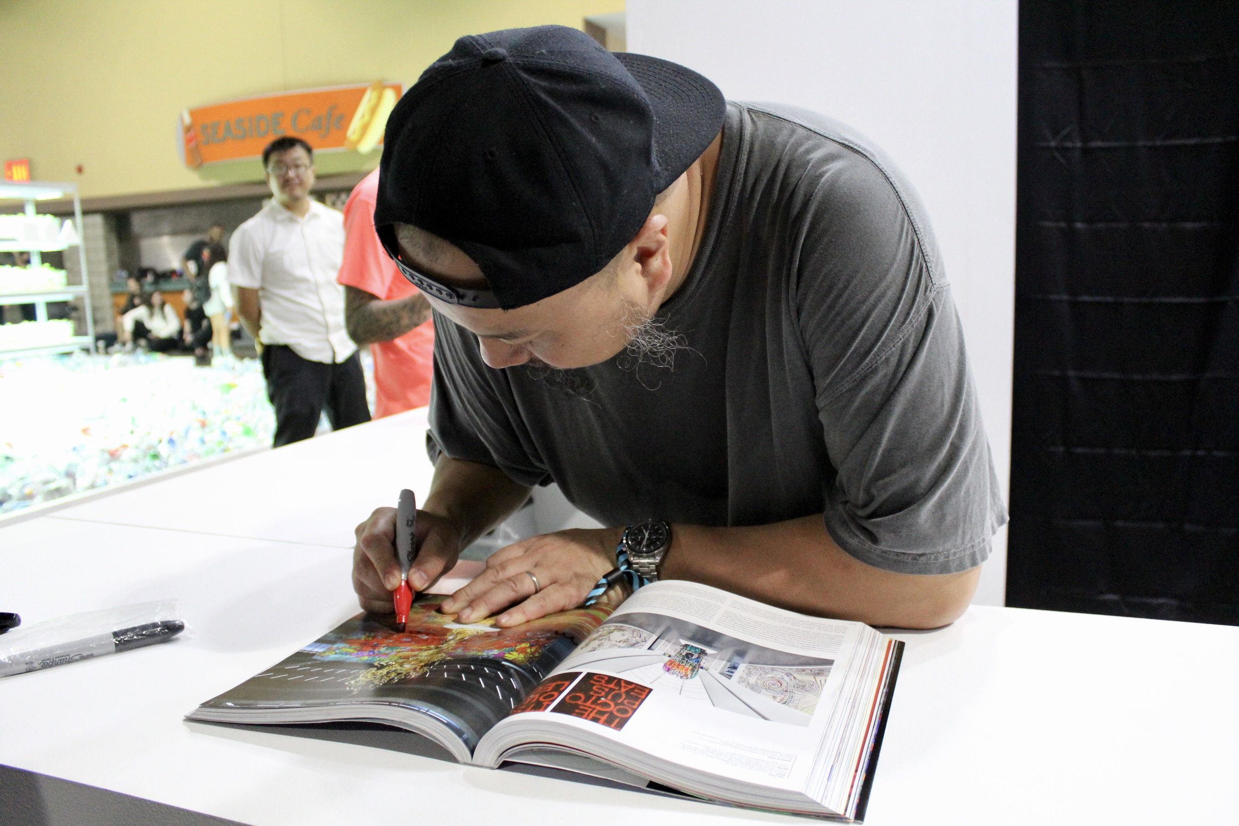 Madsaki signing our Beyond The Streets book at the Kaikai Kiki Gallery booth
