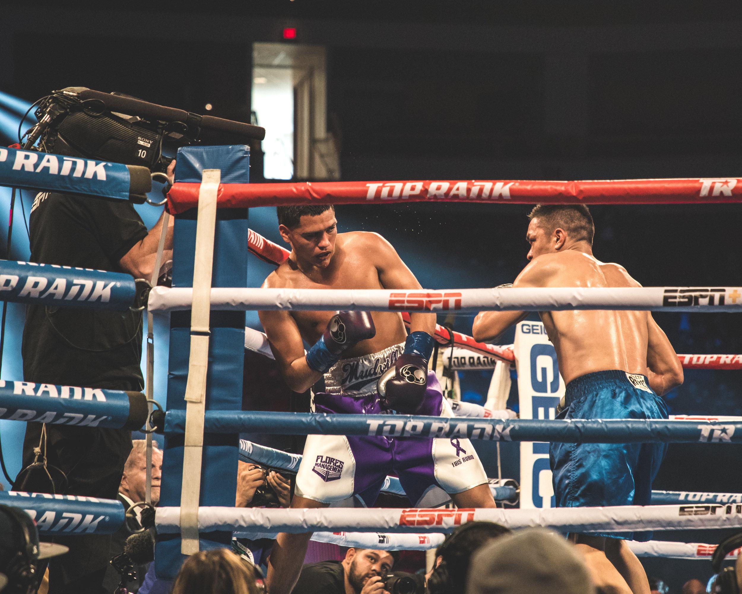 Alex Torres Rynn has Gabriel Flores Jr. against the ropes by Benny Blanco