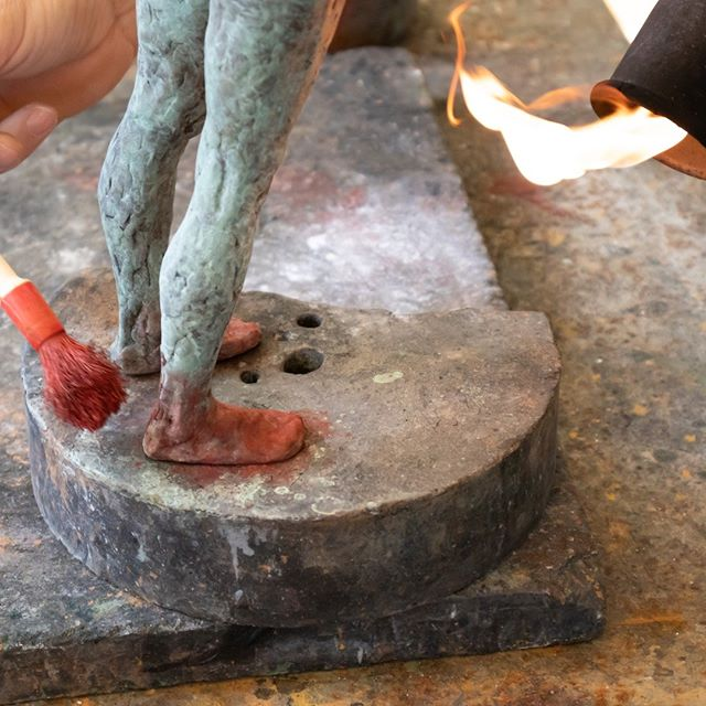Here is a bronze figure during the process of patination. Chemicals are carefully applied to the raw bronze, followed by a blast of heat from the blowtorch to create a permanent chemical reaction that changes the color on the surface of the metal. The tones are built up layer by layer to create a rich and varied final coloration. Here a layer of red is being applied over a base layer of green. Patination is an art form unto itself! #bronzesculpture #bronzesculptureprocess #figuresculpture #figurativesculpture #bronzepatina #foundry #artprocess #contemporaryrealism