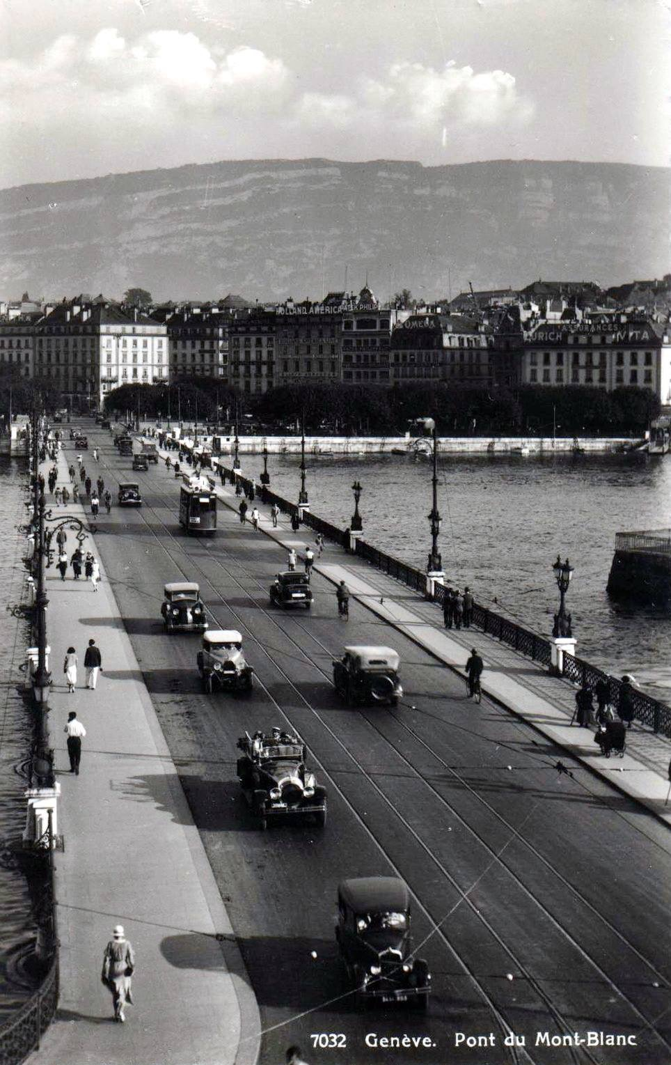 Vintage, black and white, postcard of Geneva with a view of the Mont Blanc bridge with a few cars and the Salève in the background.